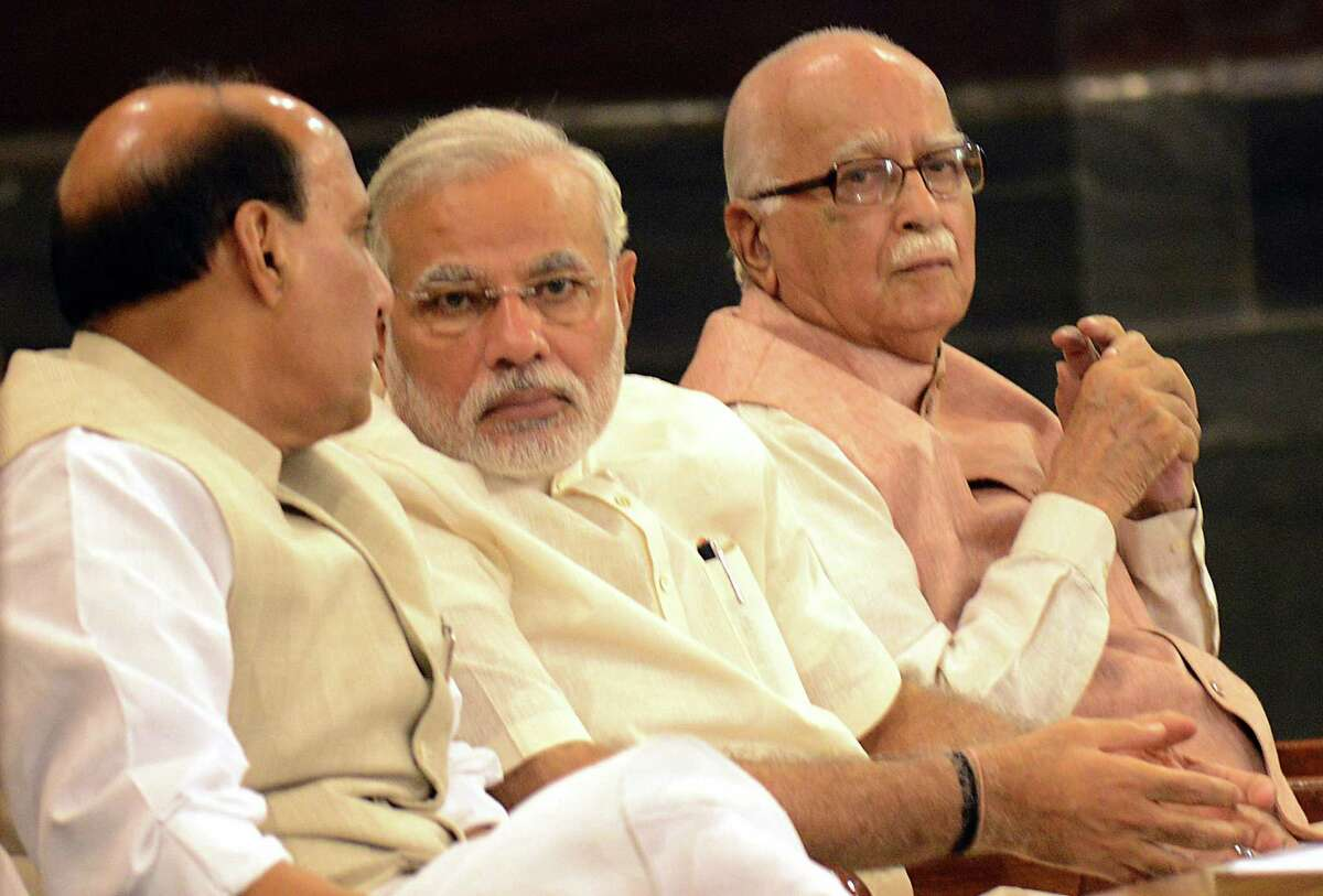 Indian Prime Minister Narendra Modi (C) talks with Bharatiya Janata Party (BJP) President and Indian Minister of Home Affairs Rajnath Singh (L) as senior BJP leader Lal Krishna Advani looks on during the BJP parliamentary party meeting in New Delhi on June 6, 2014. India's new parliament begain its first session after the national election which swept Modi's Bharatiya Janata Party (BJP) to power. AFP PHOTO/RAVEENDRANRAVEENDRAN/AFP/Getty Images