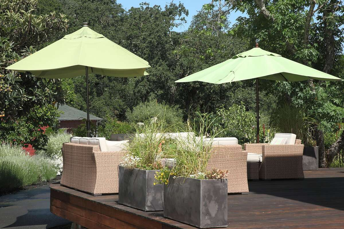 The deck sits above a concrete patio and is flanked by gardens and mature trees.Ê