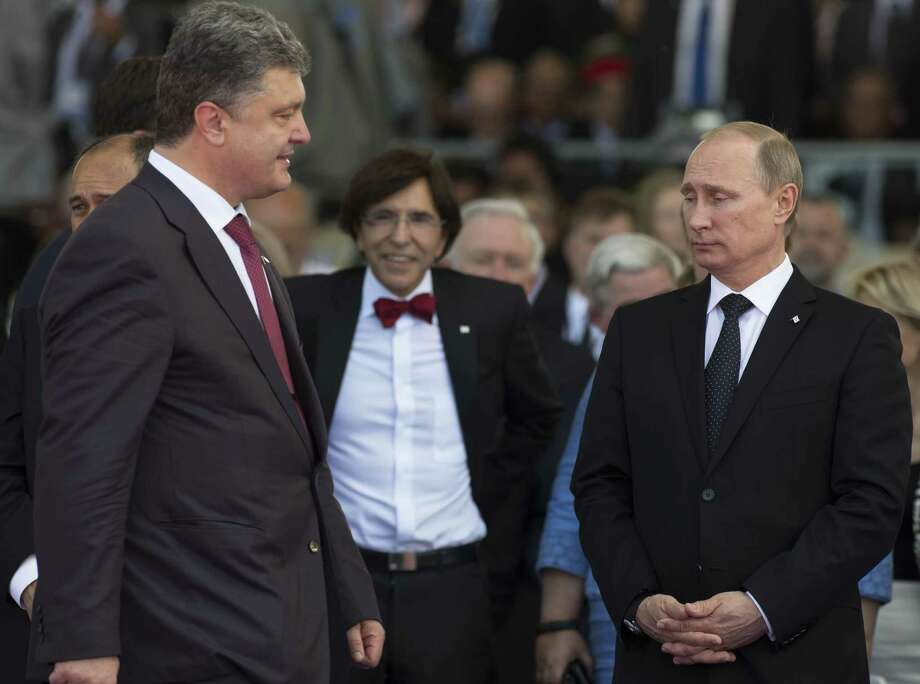 Ukraine's President-elect Petro Poroshenko (L) walks past Russia's President Vladimir Putin (R) during an international D-Day commemoration ceremony on the beach of Ouistreham, Normandy, on June 6, 2014, marking the 70th anniversary of the World War II Allied landings in Normandy.  AFP PHOTO / POOL / ALEXANDER ZEMLIANICHENKOALEXANDER ZEMLIANICHENKO/AFP/Getty Images ORG XMIT: - Photo: ALEXANDER ZEMLIANICHENKO / AFP