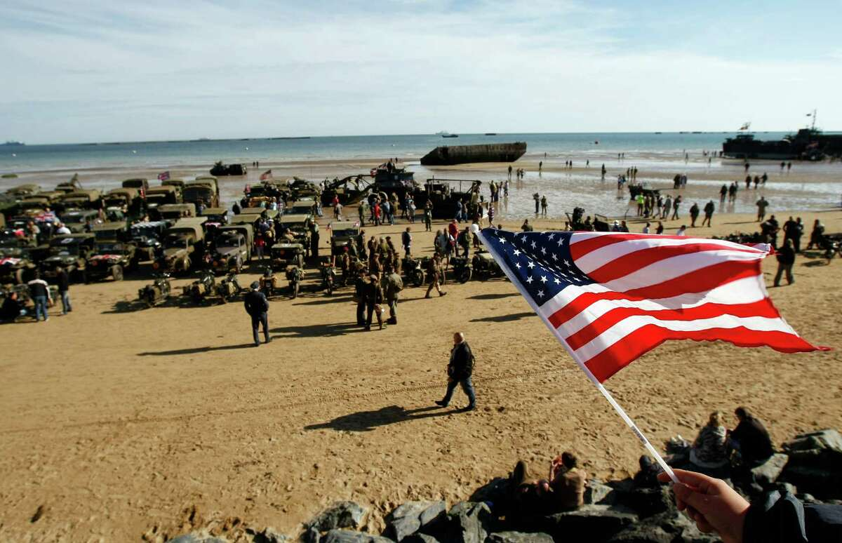 An onlooker waves an American flag as World War II military vehicles are displayed on the beach of Arromanches, France, Friday, June 6, 2014, as part of D-Day commemorations. World leaders and veterans gathered by the beaches of Normandy, northern France, on Friday to mark the 70th anniversary of the World War II D-Day landings. (AP Photo/Claude Paris) ORG XMIT: CLP139