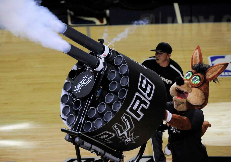 """The Spurs Coyote has a new toy: a Gatling gun capable of firing 60 T-shirts into the crowd in 10 seconds. """"They're shooting 120 shirts in a two-minute timeout,"""" said Cassidy Lien, producer of game entertainment.  PHOTO: The San Antonio Spurs Coyote fires T-shirts into the crowd during the second half of Game 1 of a Western Conference finals NBA basketball playoff series against the Oklahoma City Thunder, Monday, May 19, 2014, in San Antonio. San Antonio won 122-105. Photo: Darren Abate, Associated Press / FR115 AP"""