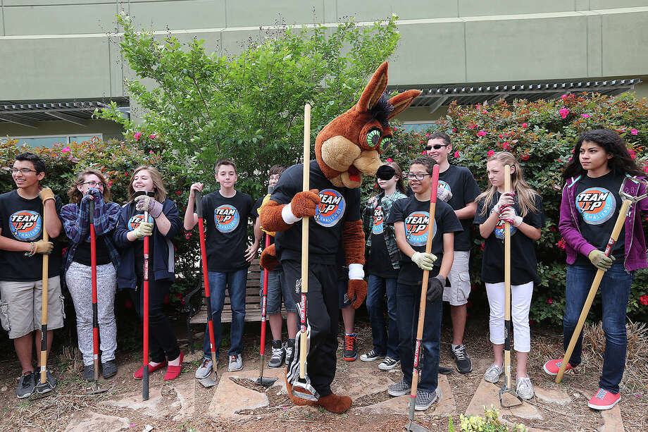 The San Antonio Spurs Coyote gets a lesson on using garden tools from the Green Team at Northeast ISD's Harris Middle School on Monday, April 14, 2014. Photo: Jerry Lara, San Antonio Express-News File Photo / ©2014 San Antonio Express-News