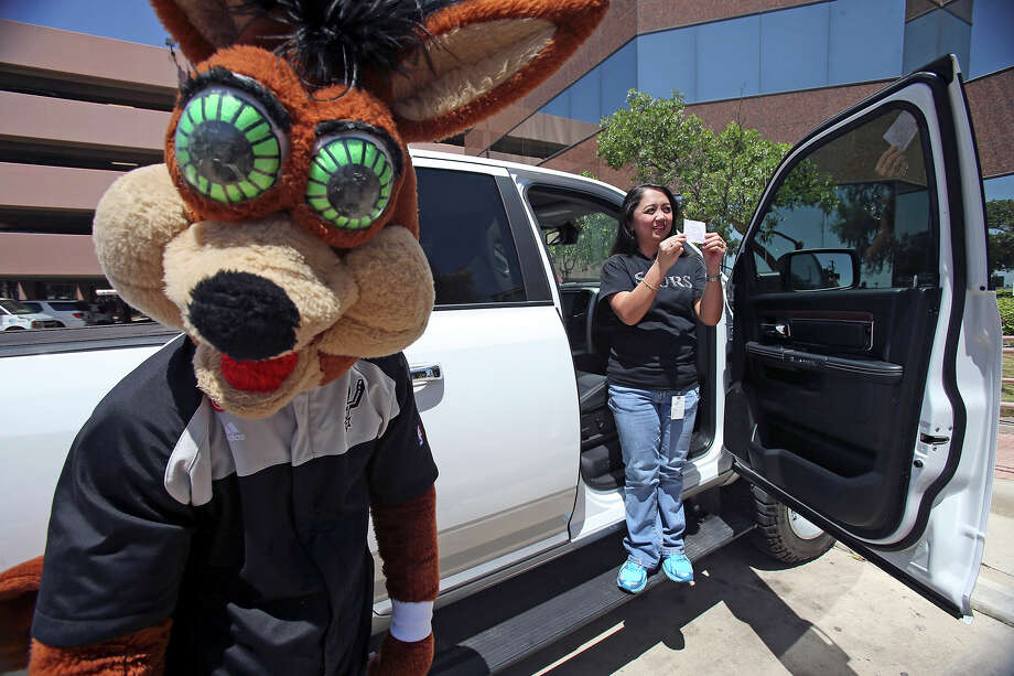 Coyote muses while Madyll Powao shows her winning raffle ticket as she takes delivery of the 2013 Ram 1500 Laramie, customized by Spurs forward Tim Duncan, on April 30, 2014. Photo: TOM REEL, San Antonio Express-News File Photo