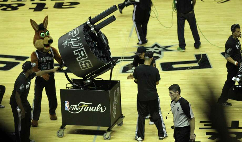 It's not surprising the Spurs Coyote was eager to get his hands on one of the new guns; he helped create the T-shirt gun in the 1990s. Read more about how the first T-shirt guns used by the Spurs Coyote and other NBA mascots came to be on ExpressNews.com.PHOTO: San Antonio Spurs fans yell for t-shirts as the Coyote gets ready to shoot the Gatling Gun during game one of the NBA Finals against the Miami Heat at the AT&T Center, Thursday, June 5, 2014. The Spurs won 110-95 to lead the series 1-0. Photo: Jerry Lara, San Antonio Express-News File Photo / ©2014 San Antonio Express-News