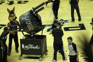 San Antonio Spurs fans yell for t-shirts as the Coyote gets ready to shoot the Gatlin Gun during game one of the NBA Finals against the Miami Heat at the AT&T Center, Thursday, June 5, 2014. The Spurs won 110-95 to lead the series 1-0.