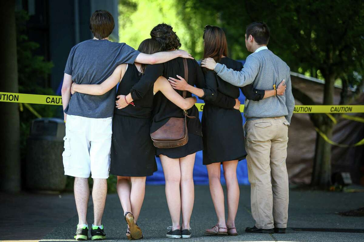 Seattle Pacific University students gather outside of Otto Miller Hall the day after a gunman shot three people on campus, killing one. Many on the campus of the Christian school have turned to prayer and their campus community during the tragedy. Photographed on Friday, June 6, 2014.