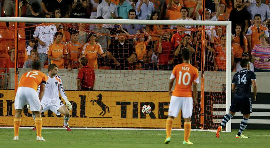Sporting Kansas City forward Dom Dwyer (14) scores on a penalty kick past Dynamo keeper Tyler Deric in the second half Friday night. Photo: Karen Warren, Staff / © 2014 Houston Chronicle
