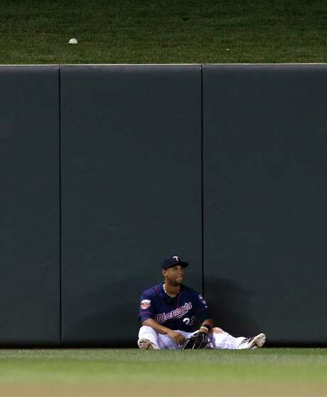 Twins center fielder Aaron Hicks finds a seat after his failed attempt to catch a solo home run by the Astros' Matt Dominguez in the fourth inning. Photo: Jim Mone, STF / AP