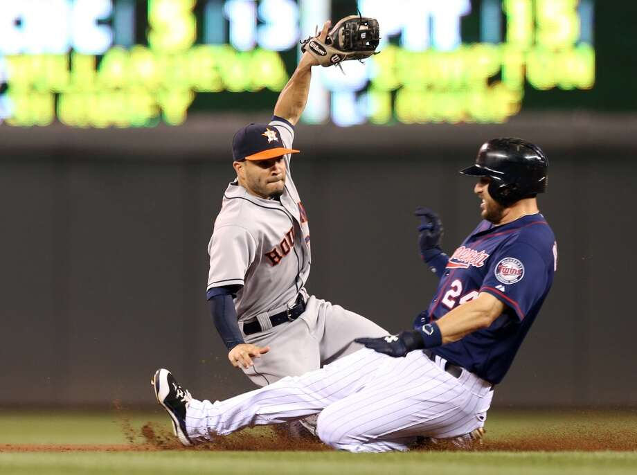 Jose Altuve, left, can't make the tag in time as Trevor Plouffe slides into second for a double in the fourth inning. Photo: Jim Mone, Associated Press