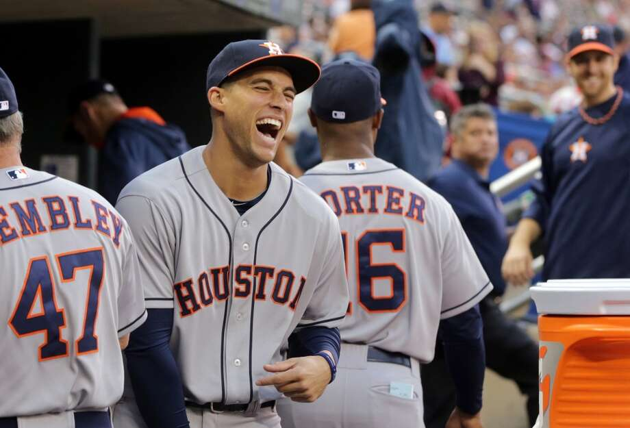 George Springer enjoys a laugh in the dugout as players waited through a weather delay. Photo: Jim Mone, Associated Press