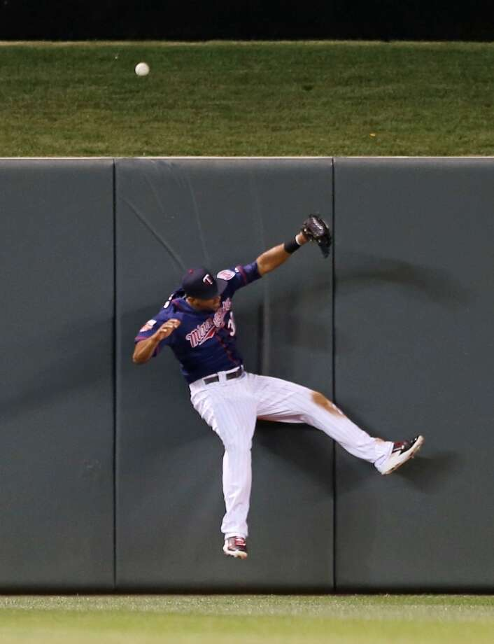 Aaron Hicks hits the wall in a failed effort to catch a solo home run in the fourth inning. Photo: Jim Mone, Associated Press