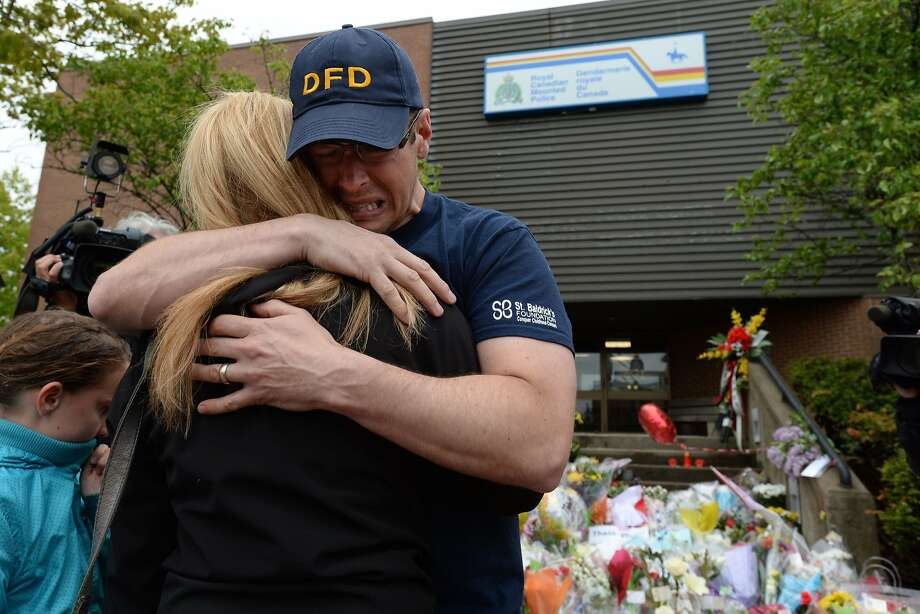 Jeff Pyke, right, is comforted after placing flowers for his friend, Constable Douglas Larche, outside Royal Canadian Mounted Police headquarters in Moncton, New Brunswick, on Friday, June 6, 2014. The suspect in the killing of three Royal Canadian Mounted Police was arrested unarmed early Friday, ending a massive manhunt that paralyzed much of the eastern Canadian city. (AP Photo/The Canadian Press, Sean Kilpatrick) Photo: Sean Kilpatrick, Associated Press