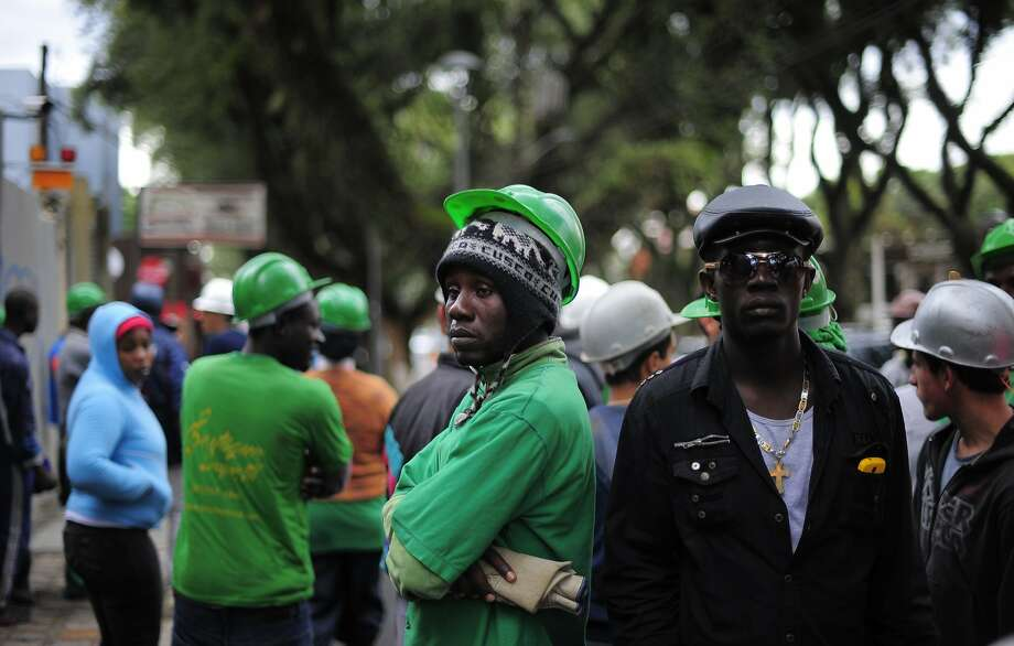 Workers protest over unpaid wages in Curitiba, Brazil, Friday, June 6, 2014. Workers briefly stopped traffic before appearing to reach an agreement in Brazil's southern city that will host four World Cup matches. Over 50 workers launched the impromptu strike at the Arena da Baixada by gathering in front of Atletico Paranaense's offices, where about two dozen of the aggrieved employees cut off traffic for about 20 minutes. A representative of the Brazilian club eventually coaxed the workers off the street and into dialogue before everyone returned inside amid signals a settlement had been reached. (AP Photo/Manu Fernandez) Photo: Manu Fernandez, Associated Press