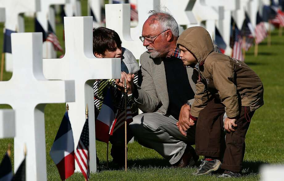 COLLEVILLE-SUR-MER, FRANCE - JUNE 06:  Michel Colas (C) shows his grandsons Samuel Colas (L) and Rafael Schneider (R) the Normandy American Cemetery before the start of an official event with U.S. President Barack Obama June 6, 2014 in Colleville-sur-Mer, France. Friday 6th June is the 70th anniversary of the D-Day landings which saw 156,000 troops from the allied countries including the United Kingdom and the United States join forces to launch an audacious attack on the beaches of Normandy,  these assaults are credited with the eventual defeat of Nazi Germany. A series of events commemorating the 70th anniversary are planned for the week with many heads of state travelling to the famous beaches to pay their respects to those who lost their lives.  (Photo by Win McNamee/Getty Images) *** BESTPIX *** Photo: Win McNamee, Getty Images