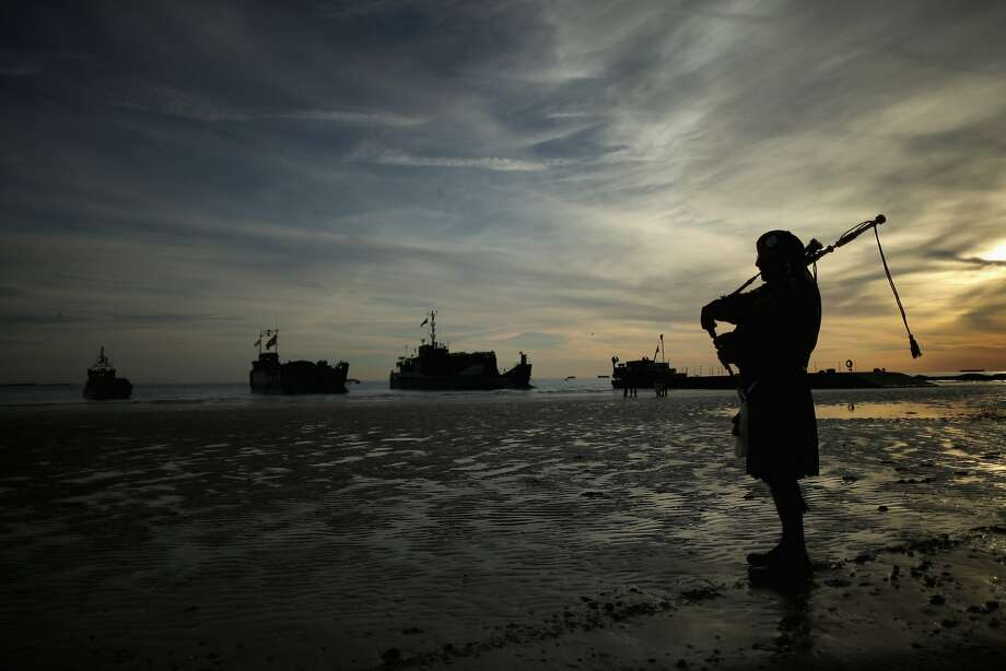ARROMANCHES LES BAINS, FRANCE - JUNE 06: A piper plays a lament on Gold Beach as landing craft from the Royal Marines arrive at Arromanche on June 6, 2014 in Arromanches Les Bains, France.  Friday 6th June is the 70th anniversary of the D-Day landings which saw 156,000 troops from the allied countries including the United Kingdom and the United States join forces to launch an audacious attack on the beaches of Normandy, these assaults are credited with the eventual defeat of Nazi Germany. A series of events commemorating the 70th anniversary are planned for the week with many heads of state travelling to the famous beaches to pay their respects to those who lost their lives.  (Photo by Christopher Furlong/Getty Images) *** BESTPIX *** Photo: Christopher Furlong, Getty Images