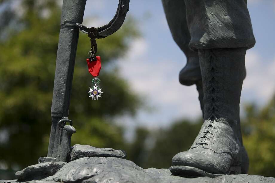 "Ash Rothlein's French Legion of Honor medal hangs from the sculpture ""Homage"" at the National D-Day Memorial in Bedford, Va., on Friday, June 6, 2014, the 70th anniversary of D-Day. Rothlein served with the 187th Advanced Army Ordnance Depot Company and helped spearhead the effort to install ""Homage"" at the National D-Day Memorial. His French Legion of Honor medal will hang each June 6 to pay tribute to those who sacrificed their life in Normandy. (AP Photo/The Roanoke Times, Erica Yoon) Photo: Erica Yoon, Associated Press"