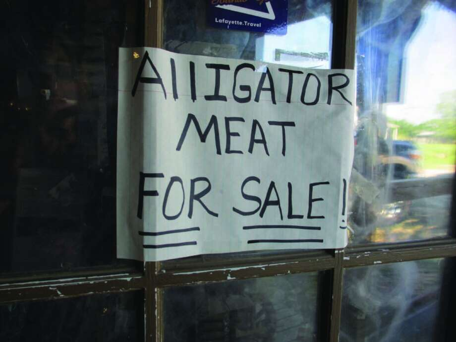 "A handwritten ""Alligator Meat For Sale"" sign was taped to a window in the Champagne's Cajun Swamp Tours office, where plenty of logo T-shifts and camo hats were for sale. We bought matching logo hats. Photo: Terry Scott Bertling, San Antonio Express-News"