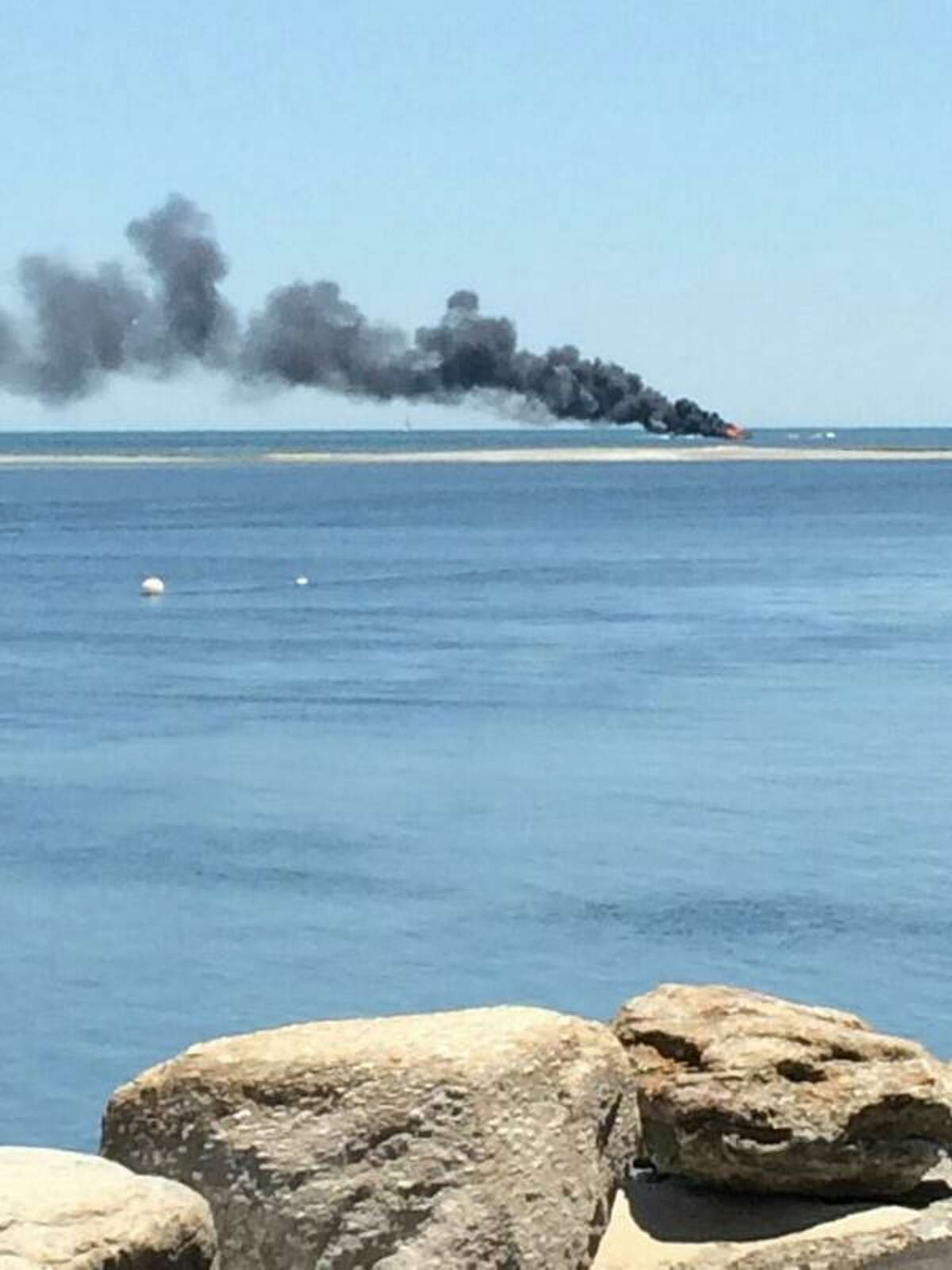 A clam board caught fire in the Housatonic River between Milford and Stratford on Saturday, June 7, 2014. Three people aboard the boat were able to escape safely onto another nearby clam boat. One of the men received third-degree burns. The burning boat is seen from Knapp's Landing in Stratford.