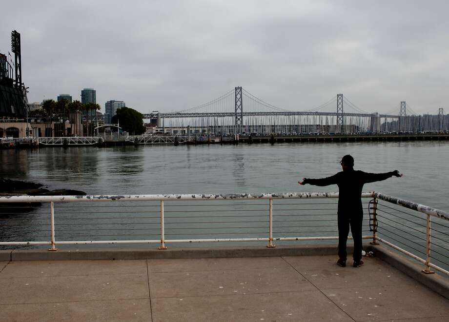 Phillipe Lochman stretches near China Basin Park and Pier 48. Bayfront water levels are forecast to rise 1 foot by 2050. Photo: Tim Hussin, Special To The Chronicle