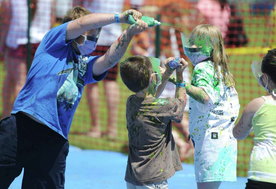"Emmet Tredennick, left, 8, of Bridgewater, Owen Maynard, center, 6, of Washington, and Abby Wayland, 9, of Warren, participate in a ""splatter Battle"" at Paint the People 2014 at the John Pettibone School in New Milford, Conn. Saturday, June 7, 2014.  Paint the People, sponsored by the Village Center for the Arts in New Milford, featured many fun paint activities for kids including splatter battles, a paint-stacle course, a public mural, paint twister, spin art, an art show and paint-along demonstrations. Photo: Tyler Sizemore / The News-Times"
