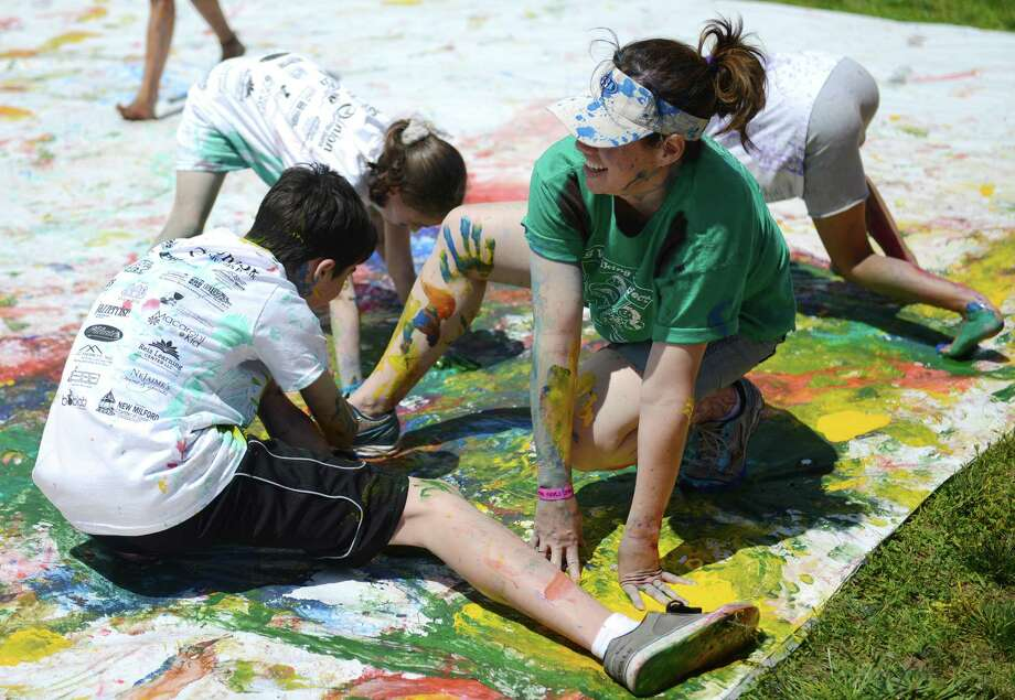 Jennifer Lipari, of New Milford, participates in paint twister with her son, Alex Lipari, 12, at Paint the People 2014 at the John Pettibone School in New Milford, Conn. Saturday, June 7, 2014.  Paint the People, sponsored by the Village Center for the Arts in New Milford, featured many fun paint activities for kids including splatter battles, a paint-stacle course, a public mural, paint twister, spin art, an art show and paint-along demonstrations. Photo: Tyler Sizemore / The News-Times