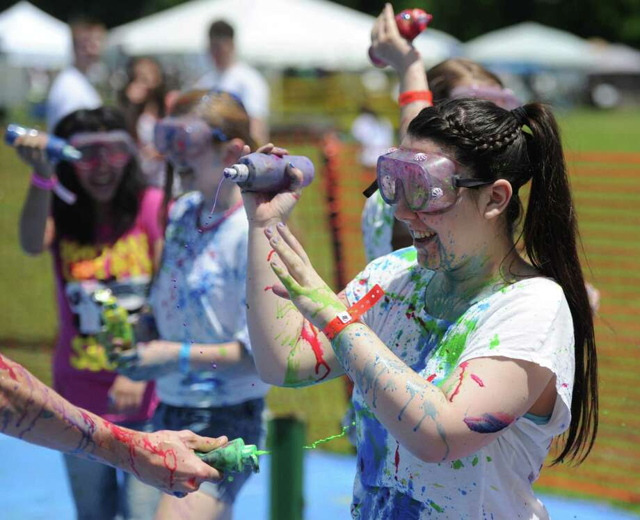 "Rachel Belcourt, 15, of New Milford, participates in a ""splatter battle"" at Paint the People 2014 at the John Pettibone School in New Milford, Conn. Saturday, June 7, 2014.  Paint the People, sponsored by the Village Center for the Arts in New Milford, featured many fun paint activities for kids including splatter battles, a paint-stacle course, a public mural, paint twister, spin art, an art show and paint-along demonstrations. Photo: Tyler Sizemore / The News-Times"
