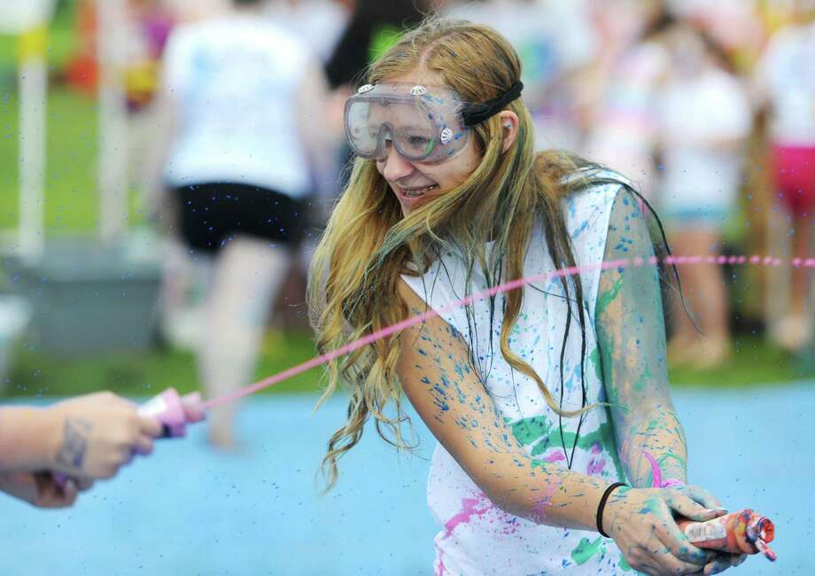 "Brittney Dubert, 16, of New Milford, participates in a ""splatter battle"" at Paint the People 2014 at the John Pettibone School in New Milford, Conn. Saturday, June 7, 2014.  Paint the People, sponsored by the Village Center for the Arts in New Milford, featured many fun paint activities for kids including splatter battles, a paint-stacle course, a public mural, paint twister, spin art, an art show and paint-along demonstrations. Photo: Tyler Sizemore / The News-Times"