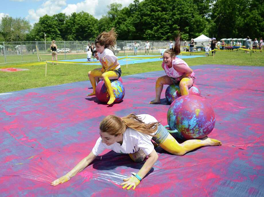 Jaclyn Bonomo, 15, of New Milford, faceplants during a bouncy ball race with her friends Olivia Kibry, left, 14, of New Milford, and Avery Kelly, 14, of New Milford, at Paint the People 2014 at the John Pettibone School in New Milford, Conn. Saturday, June 7, 2014.  Paint the People, sponsored by the Village Center for the Arts in New Milford, featured many fun paint activities for kids including splatter battles, a paint-stacle course, a public mural, paint twister, spin art, an art show and paint-along demonstrations. Photo: Tyler Sizemore / The News-Times