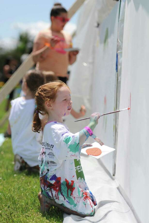 Makenzie Maxwell, 4, of New Milford, paints on the group mural wall at Paint the People 2014 at the John Pettibone School in New Milford, Conn. Saturday, June 7, 2014.  Paint the People, sponsored by the Village Center for the Arts in New Milford, featured many fun paint activities for kids including splatter battles, a paint-stacle course, a public mural, paint twister, spin art, an art show and paint-along demonstrations. Photo: Tyler Sizemore / The News-Times