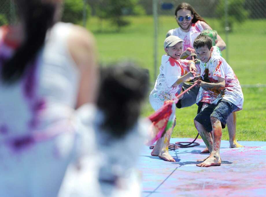 Paint the People attendees participate in tug-of-war at the John Pettibone School in New Milford, Conn. Saturday, June 7, 2014.  Paint the People, sponsored by the Village Center for the Arts in New Milford, featured many fun paint activities for kids including splatter battles, a paint-stacle course, a public mural, paint twister, spin art, an art show and paint-along demonstrations. Photo: Tyler Sizemore / The News-Times
