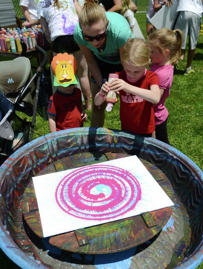 Sarah Kelley, 6, of Patterson, N.Y., creates paint spin art at Paint the People 2014 at the John Pettibone School in New Milford, Conn. Saturday, June 7, 2014.  Paint the People, sponsored by the Village Center for the Arts in New Milford, featured many fun paint activities for kids including splatter battles, a paint-stacle course, a public mural, paint twister, spin art, an art show and paint-along demonstrations. Photo: Tyler Sizemore / The News-Times