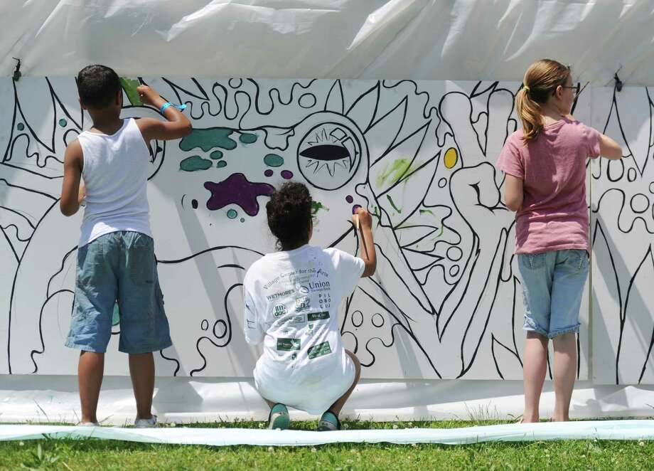 Jaden Taronji, 12, of Bronx, N.Y., Jailene Urena, 15, of Bronx, N.Y., and Annabelle Colonna, 10, of New Milford, paint the group mural at Paint the People 2014 at the John Pettibone School in New Milford, Conn. Saturday, June 7, 2014.  Paint the People, sponsored by the Village Center for the Arts in New Milford, featured many fun paint activities for kids including splatter battles, a paint-stacle course, a public mural, paint twister, spin art, an art show and paint-along demonstrations. Photo: Tyler Sizemore / The News-Times