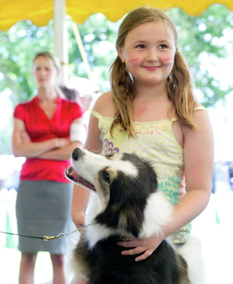 Jaime McDonald, 7, of Fairfield, gets a hug from border collie Karma, owned by Kari Streicher of Moodus, Conn., during the Greenwich Kennel Club's All-Breed Dog Show at Calf Pasture Beach in Norwalk, Conn., on Saturday, June 7, 2014. Photo: Lindsay Perry / Stamford Advocate