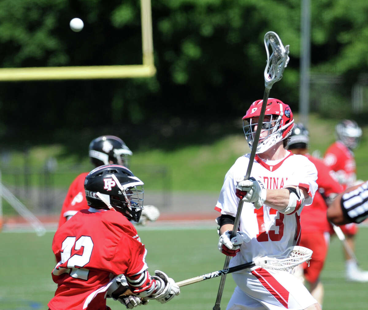 At right, Jack Nail of Greenwich (#13) passes as John Edmonds (#22) of Fairfield Prep defends during the Class L boys high school lacrosse quarterfinal match between Fairfield Prep and Greenwich High School at Greenwich, Saturday, June 7, 2014. Greenwich won the match, 9-8, advancing to the semi-final.