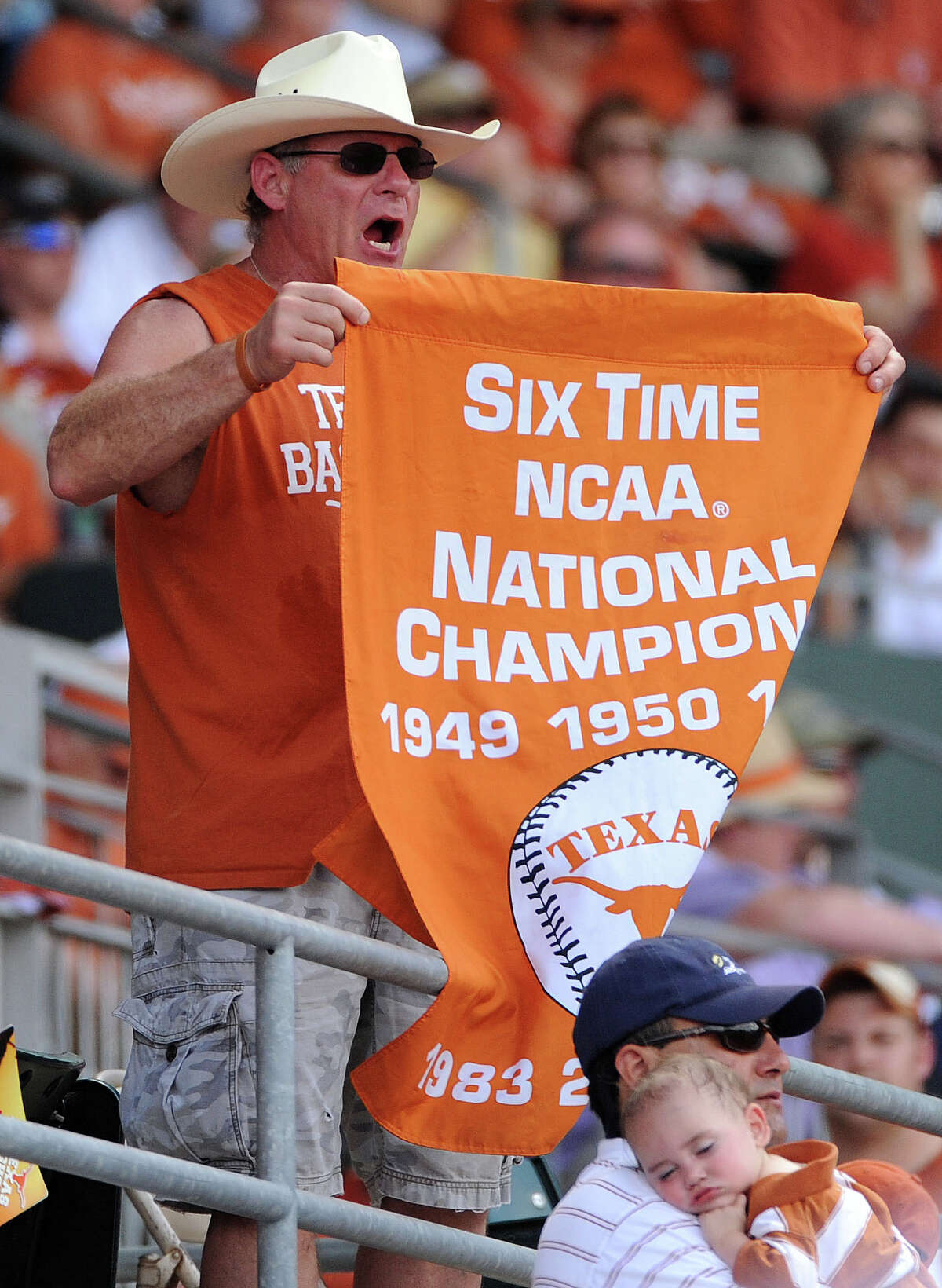 A fan of the Texas Longhorns hold a banner signifying the Longhorns' six national championships during the ninth inning of an NCAA baseball super regional game against Houston, Saturday, June 7, 2014, at UFCU Disch-Falk Field in Austin.