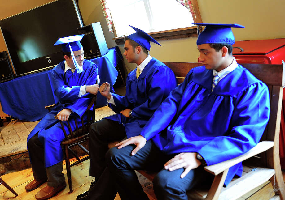 Stephen Cardone, left, of Trumbull, and his fellow classmate Ian Vaca, center, of Southport, bump fists before the start of the 31st Commencement Exercises of Christian Heritage School in Trumbull, Conn. on Saturday June 7, 2014. At right is classmate Ezequiel Wangaard, of Shelton. Photo: Christian Abraham / Connecticut Post