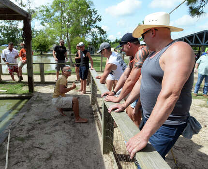 Tillman Hoffpauir, front, and others watch Andrew Austin manage some of the spiny soft-shell turtles at Gator Country on Saturday morning. The 2014 Gator Rescue Tournament was held at Gator Country on Saturday. Photo taken Saturday 6/7/14 Jake Daniels/@JakeD_in_SETX Photo: Jake Daniels / ©2014 The Beaumont Enterprise/Jake Daniels