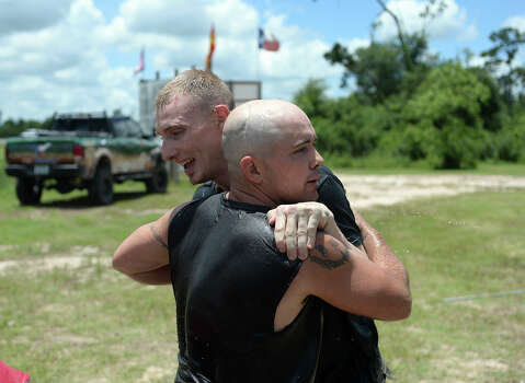 Jason Boudoin, front, hugs teammate Jonathan Osborne after they finish the second event of Saturday's Gator Rescue Tournament. The 2014 Gator Rescue Tournament was held at Gator Country on Saturday. Photo taken Saturday 6/7/14 Jake Daniels/@JakeD_in_SETX Photo: Jake Daniels / ©2014 The Beaumont Enterprise/Jake Daniels