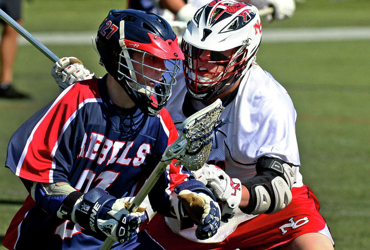 New Fairfield's Liam Rattigan runs up against New Canaan's David Strupp, during Class M Boys Lacrosse Quarterfinal action in New Canaan, Conn. on Saturday June 7, 2014.