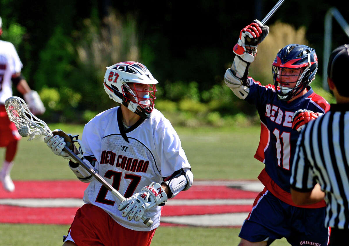 New Canaan's Clayton Burt drives towards the goal as New Fairfield's Steven Conrad looks to block, during Class M Boys Lacrosse Quarterfinal action in New Canaan, Conn. on Saturday June 7, 2014.
