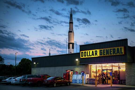 A replica of a Saturn V rocket in the Rocket Park at the U.S. Space & Rocket Center rises above a nearby store on in Huntsville, Ala., ground zero for U.S. rocketry, and where NASA is designing its biggest ever to take astronauts farther.