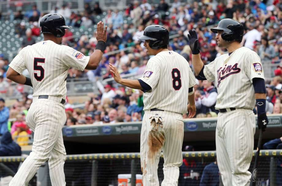 Eduardo Escobar, left, and Kurt Suzuki, center, score on a double by Danny Santana. Photo: Jim Mone, Associated Press