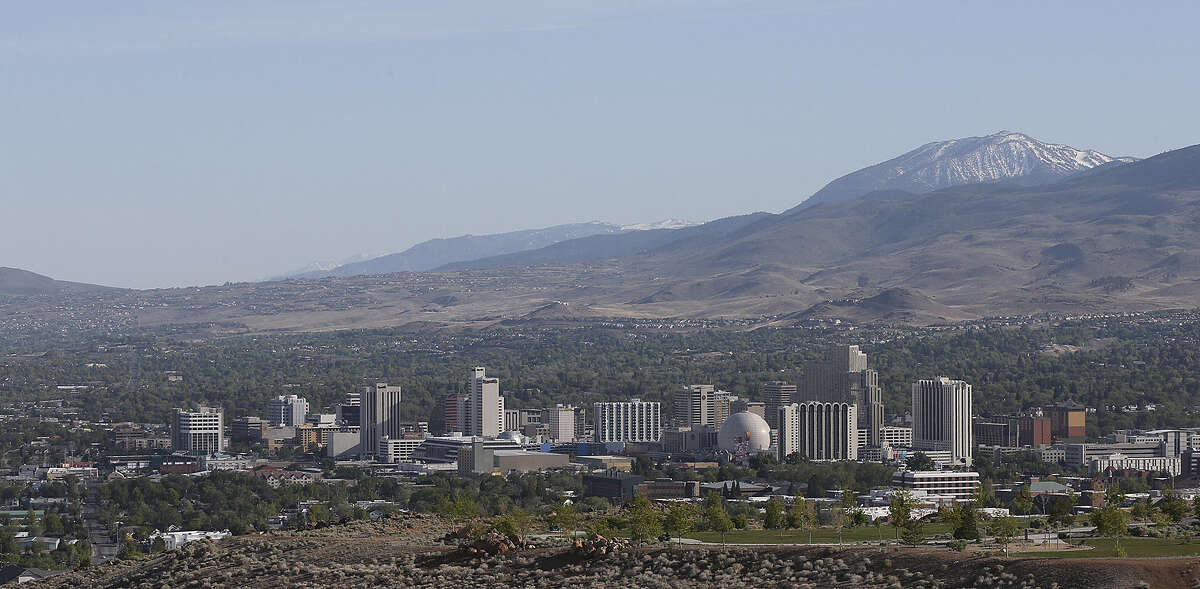 """Sunset lights downtown Reno, Nevada with the Sierra Nevada in the background. According to news reports, Tesla Motors Inc. has selected Nevada for the site of its planned $5 billion """"gigafactory."""" Tesla last month confirmed that it had broken ground in Reno."""