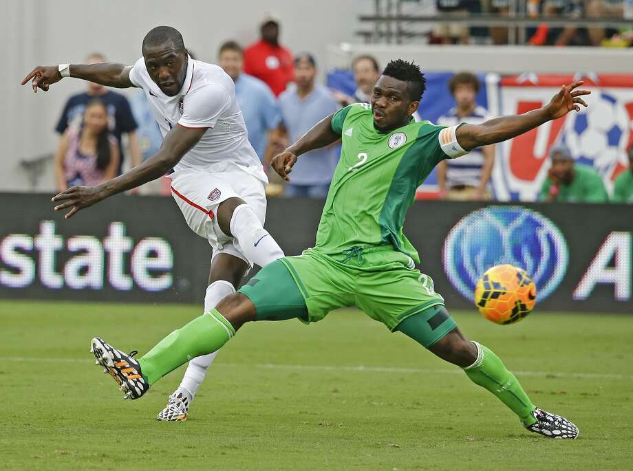 Jozy Altidore (left) scores a goal as he kicks the ball past Nigeria's Joseph Yobo during the second half. Photo: John Raoux, Associated Press