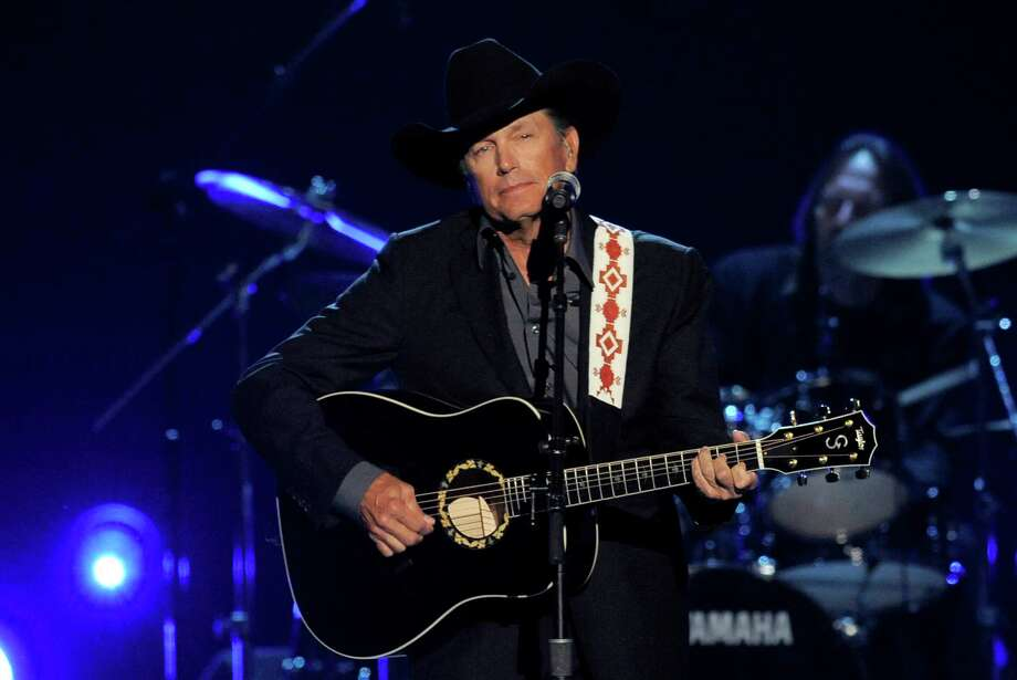 This April 7, 2013 file photo shows George Strait performing at the 48th Annual Academy of Country Music Awards at the MGM Grand Garden Arena in Las Vegas.   It's the end of the trail for country music king George Strait, who will wrap up his final tour Saturday, June 7, 2014with a star-filled show at the lavish home of the Dallas Cowboys in his home state of Texas. The show brings an end to nearly 40 years on the road for Strait, which started in 1975 with the Ace in the Hole Band.   He's had more songs top Billboard's country music charts than any other musician. And while he's quitting the road he may yet add to his total after renewing his deal with MCA Records last year to produce five more albums. (Photo by Chris Pizzello/Invision/AP, File) Photo: Chris Pizzello, INVL / Invision