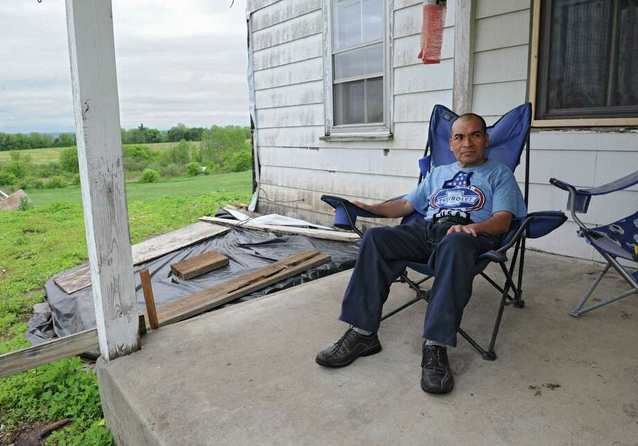 Dairy farm worker Lazaro Alvarez sits on the porch of his home near the dairy farm he now works on Tuesday, May 27, 2014 in Fonda, N.Y. Alvarez was fired from his previous job in Chenango county where he was attacked and injured by a bull. (Lori Van Buren / Times Union) Photo: Lori Van Buren / 00027071A