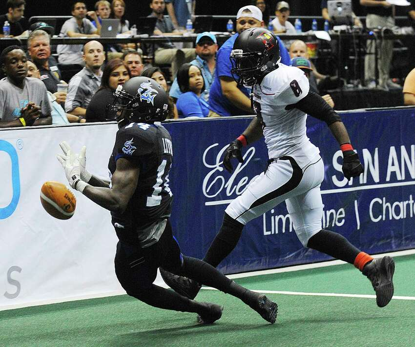 David Little of the San Antonio Talons drops the ball as Quentin Sims of the Orlando Predators defends during Arena Football League action in the Alamodome on Saturday, June 7, 2014. Sims was called for pass interference.