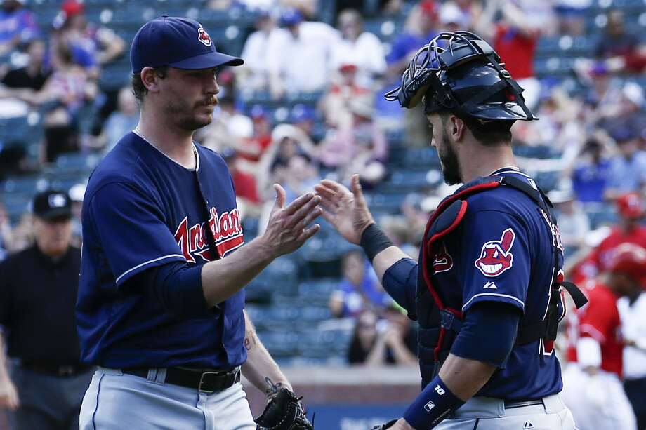Indians reliever John Axford (left) and catcher Yan Gomes congratulate each other after Saturday's win. Photo: Jim Cowsert / Associated Press / FR170531 AP