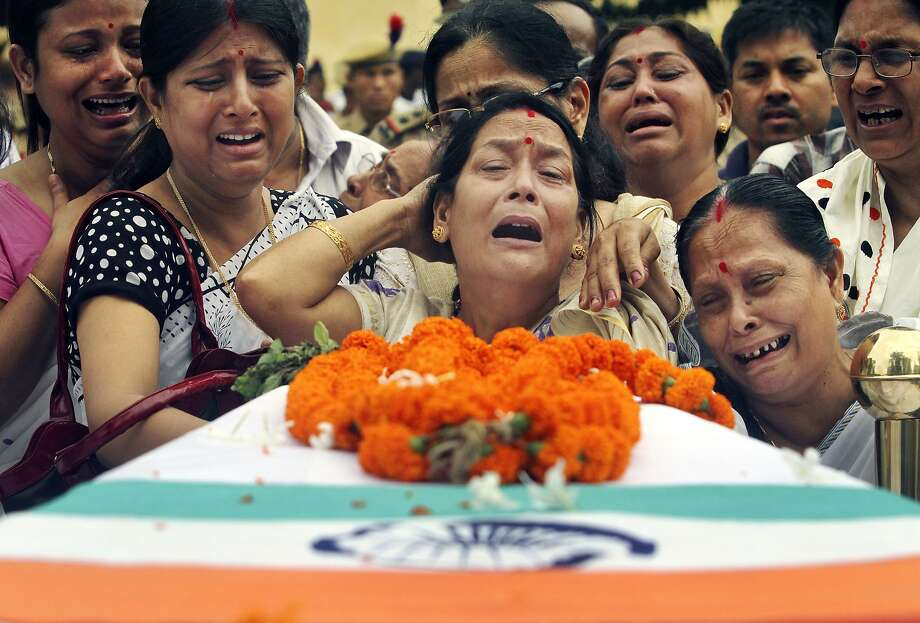 Relatives mourn by the coffin containing the body of Superintendent of Police (SP) of Hamren police district of Karbi, Anglong Nityananda Goswami, who was killed in a rebel attack, as they load his body in a vehicle during his guard of honor function at the 4th Assam Police Battalion Headquarter in Gauhati, India, Saturday, June 7, 2014. Suspected insurgents have ambushed and killed two policemen in the rebels' stronghold in India's remote northeast. Photo: Anupam Nath, Associated Press