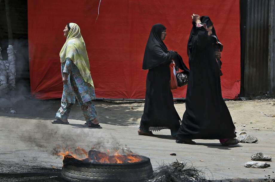 Kashmiri Muslim women walk past a burning tire set up as road blockade during a protest in Srinagar, India, Saturday, June 7, 2014. Dozens of residents in Indian portion of Kashmir blocked the road and protested against the police who arrested a youth in Srinagar Saturday, according to local news reports.  Photo: Dar Yasin, Associated Press